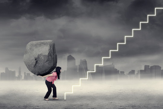 Strong worker with boulder climbs stairs