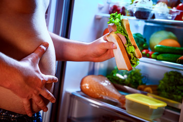 Hungry man holding a sandwich in his hands and standing next to the open fridge.