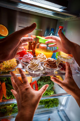 Human hands reaching for sweet cake at night in the open refrigerator