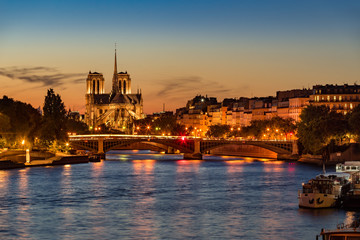 Notre Dame de Paris Cathedral, Seine River and the Ile Saint Louis at twilight. Summer evening with the Sully Bridge and city lights in the 4th Arrondissement of Paris. France