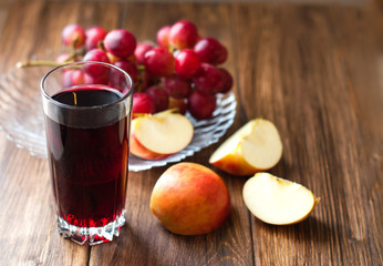 Grape juice in a glass beaker, grapes and apples on a wooden background. Fruit mix