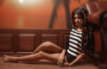 Slim girl sitting on the floor against the wall with wood paneling and Wallpaper.