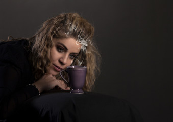 Beautiful girl with cup of coffee, hot chocolate or tea in a bed