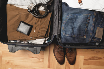 Open traveler's bag with men clothing, accessories, wallet, leather shoes and belt. Travel and vacations concept.