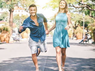 Couple holding hands while running