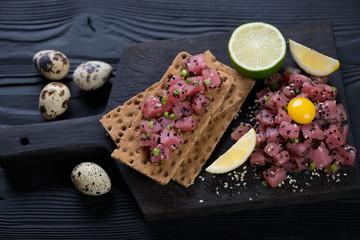 Black wooden serving board with fresh tuna tartare, selective focus, studio shot
