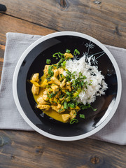 Delicious turkey mango curry with rice on a black plate
