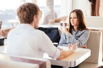 Millennial couple fighting arguing in coffee shop