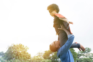 Father holding and helping flying super hero kid togehter in happiness