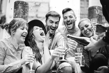 Group of friends having a party in the city drinking champagne