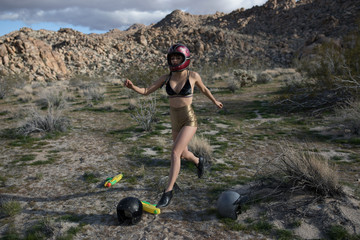 Woman kicks a helmet out in the desert