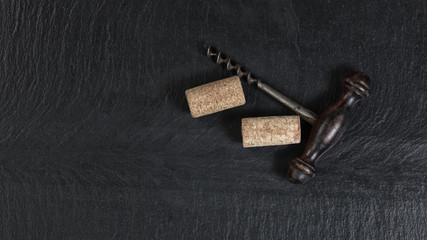 Overhead view of vintage corkscrew on black slate background