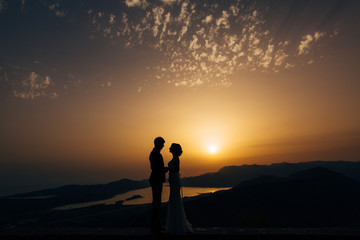 Silhouette of the newlyweds against the sky at sunset. Wedding in Montenegro. Silhouette of a couple. Silhouette of the bride and groom.