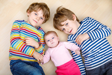 Two happy little preschool kids boys with newborn baby girl