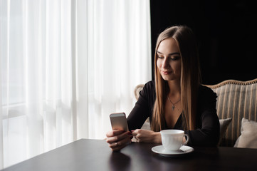 Portrait of young businesswoman use mobile phone while sitting in comfortable coffee shop during work break