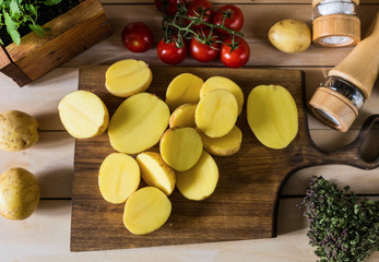 Sliced raw potato on wooden cutting board top view