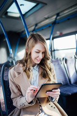 Beautiful young woman smiling, sitting in city bus and looking at tablet.
