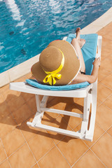 Woman in hat relaxing in a lounger at the poolside