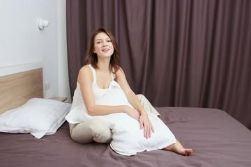 Beautiful smiling caucasian girl having fun in bed at the morning.