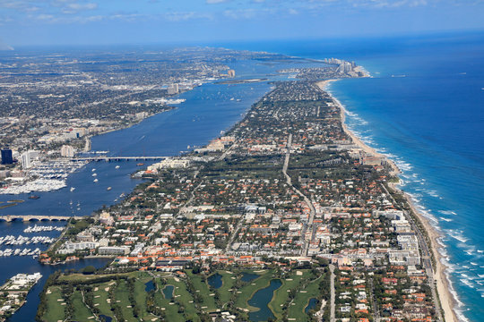 Aerial view of beautiful Palm Beach and Singer Island, Florida, along with the Atlantic Ocean, and the red roof tops of Worth Avenue.