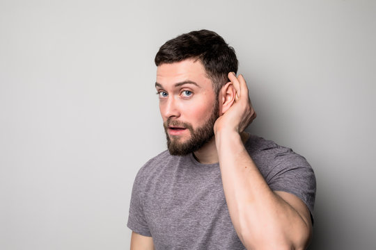 Closeup portrait a man placing hand on ear listening carefully isolated on gray wall background.