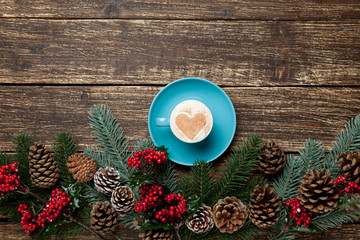 photo of cup of coffee near christmas decorations on the wonderful brown wooden background