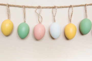 Easter eggs hanging on rope over wooden background.