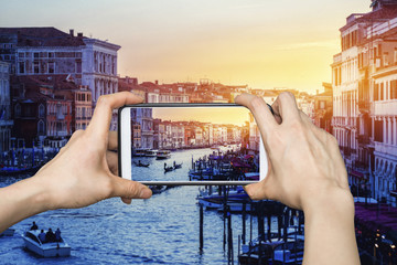 Tourist using  smartphone taking a photo of Grand Canal at sunset in Venice, Italy