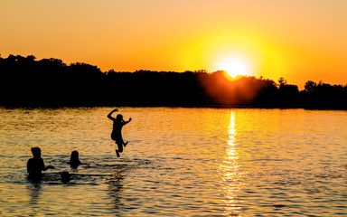 People are having fun in a lake under sunset