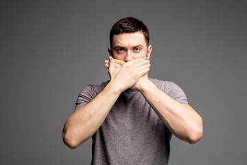 Young man keep his mouth closed by his hands on grey background.