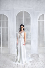 Beauty portrait of bride wearing fashion wedding dress with feathers with luxury delight make-up and hairstyle, studio indoor photo.
