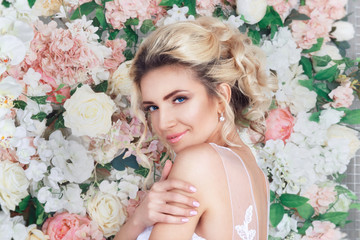 Portrait of a beautiful fashion bride, sweet and sensual. Wedding make up and hair. Flowers background. Art modern style. Blue eyes.