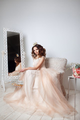 Beautiful bride posing in peach wedding dress sitting on sofa in a white photo Studio.