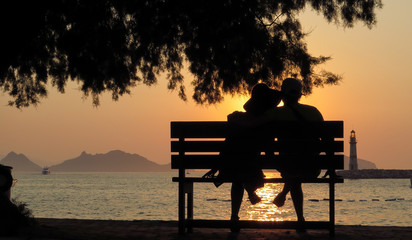 Loving people on the bench in silhouette