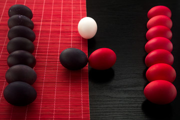 Red, dark violet or black and white easter eggs on a red bamboo napkin on a textured black wooden background. The concept of a holiday and a happy Easter. With space for text