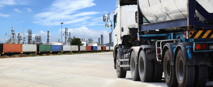 Freight Train Backdrop oil refinery and silver tanker lorry or truck in parking