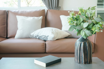 Light brown leather sofa with vase and book on center table