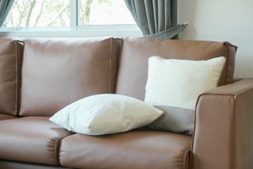 Close up pillows on brown leather sofa
