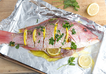 whole red snapper with lemon slices and parsley
