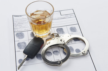 Handcuffs with fingerprints keys and glass of alcohol on ice
