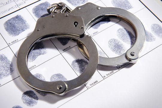 Handcuffs laying on top of fingerprint chart