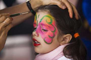 Little girl having face painted on party