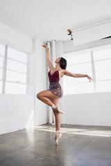 Beautiful young woman is dancing in studio