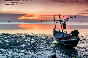 Beautiful seascape. Old wooden fishing boat on the shoal on the beach against the sunset background