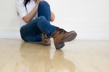 Legs of women wearing jeans brown boots.