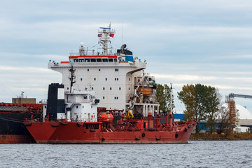 Red cargo ship loading in the port of Riga, Europe