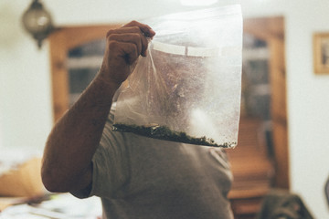 A man with a plastic bag of cannabis