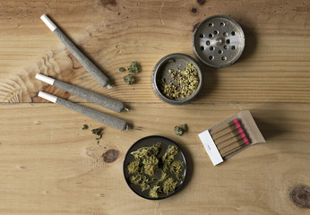 Overhead view of grinder, joints, cannabis buds and matches