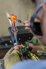 Close up of glassblower creating a glass pipe