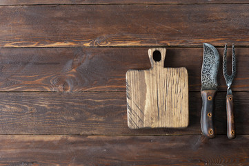 wooden background with a knife and fork for meat